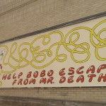 A large billboard, 8' x 24'. Death with a scythe chases a clown into an endlessly-looped maze. Text: Help Bobo Escape from Mr. Death! (there is no escape)