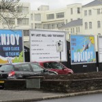 "Four large billboards in Birmingham, UK. Two of them look like 30's travel posters in bright colors with the captions ""ENJOY your clock is ticking"" and ""death takes no HOLIDAY"". The two other billboards are all fill-in-the-blank text: My Last Will and Testament and Obituary"