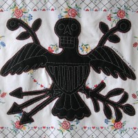 From the series American Memento Mori: Eagle - applique and embroidery on vintage textile. A folk art figure of an eagle in silhouette with a skeleton head is appliquéd onto a colorful vintage tablecloth, and embellished with white embroidery.
