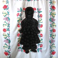 From the series American Memento Mori: Doll - applique and embroidery on vintage textile. A folk art doll silhouette with a skeleton head is appliquéd onto a colorful vintage tablecloth, and embellished with white embroidery.