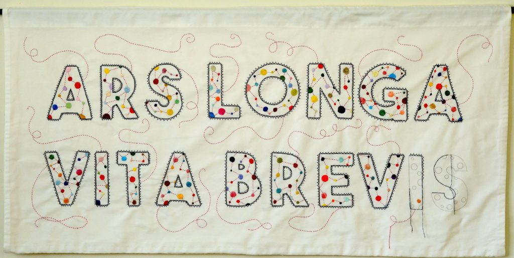 """Exuberant lettering of """"ARS LONGA VITA BREVIS"""" (art is long, life is short). The work is unfinished to show that the artist has been """"called away""""."""
