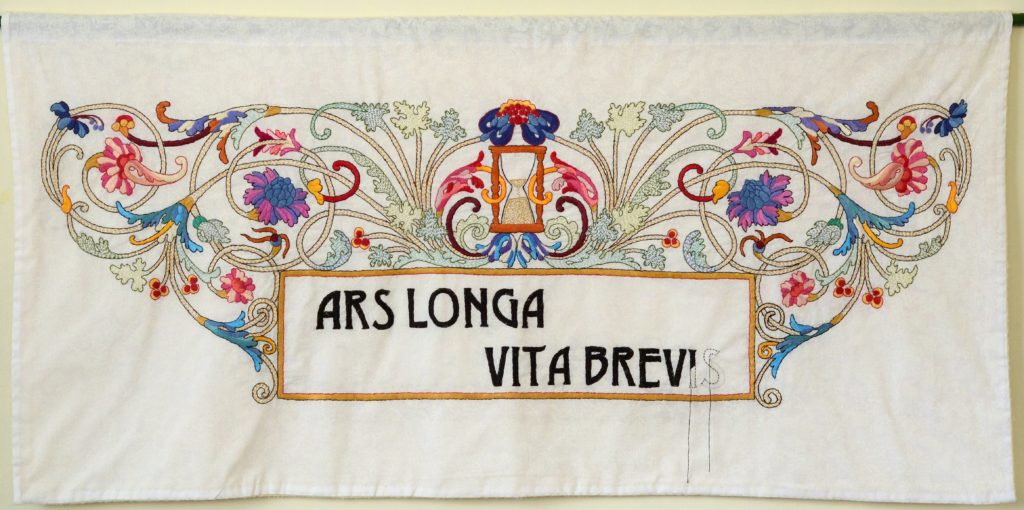 """Elaborate cartouch containing the words """"ARS LONGA VITA BREVIS"""" (art is long, life is short). The work is unfinished to show that the artist has been """"called away""""."""